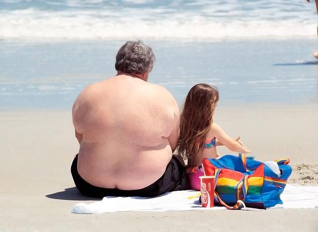 Un hombre obeso descansa en una playa con una bebida azucarada / Kyle May